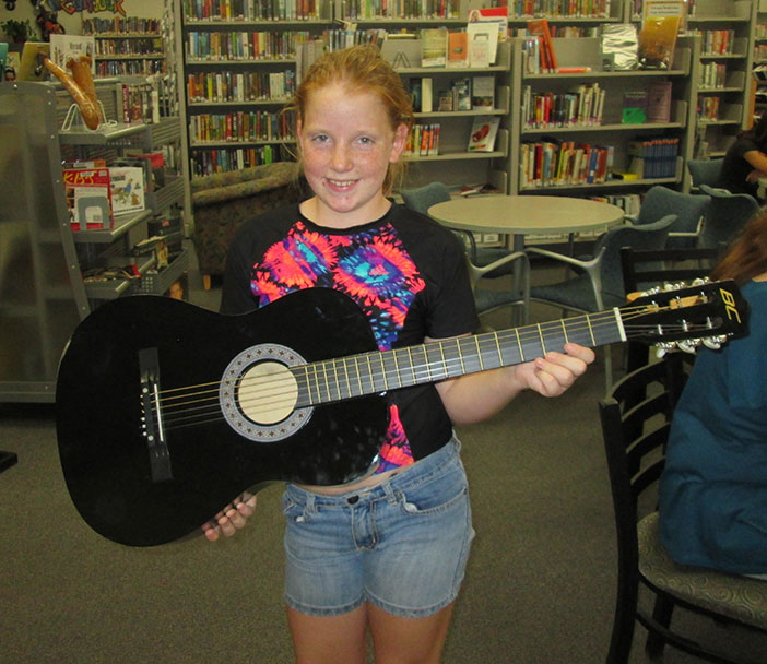 "Abbey Patrick was pleased to win a guitar in the Library's Summer Reading Program, ""Reading to the Rhythm."" Photo by Sandra Brautigam."