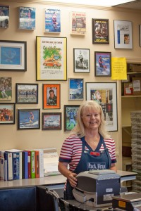 Debby stands in front of her Wall of Fame, which contains pictures of such local heroes as Rhoni Barton, Tony Klarich, Scott Larson, Melissa Marquardt, Chip Foose, Bob Kielty, Joe Young, Tori Kelly, Chef Anton and Tony Arendt, to name a few. Photo by Amy Golding.