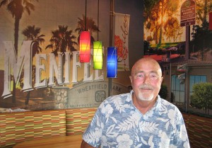 In September 2014, Canyon Lake photographer Mike Clary posed in front of two of the murals created with his photographs at the newly opened Applebee's in Menifee.