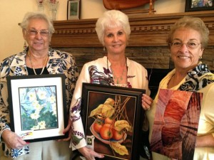 Artists Marge Wicen, Christy Bruce and Leann Kluck are seen holding their respective work.