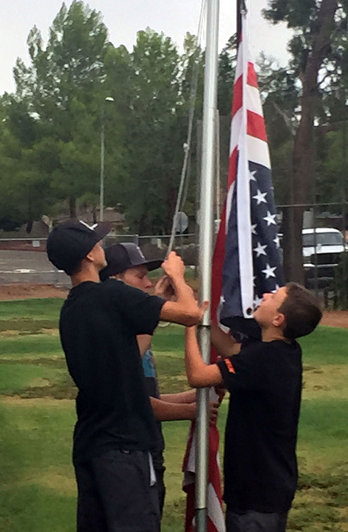 Justin Gerlek, Conner Felt and Ethan Clark noticed the U.S. flag hanging upside down and almost dragging on the ground at Gault Field after the September 9 storm. They retrieved the flag and folded it in the proper way they learned as Cub Scouts.