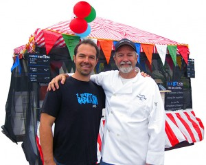 """Kasey Crawford, pastor of Elevation Church, and his dad, Ken Crawford, are pictured in front of the Elevation booth at Fiesta Day, where they served up Ken's famous """"Bingo's BBQ Glory"""" ribs. Photo by Sharon Rice"""