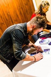 He's also seen signing autographs, something he normally isn't accustomed to doing at concerts. . Photo by Mike Clary.