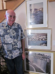 Ben stands with framed photos of the lake, including one of the old dam as it looked when he joined the EVMWD board of directors.  Photos by Sharon Rice.
