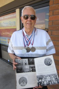 Wearing his Firemen's Olympics medals, Jack shows the yearbook page where he was named outstanding high school swimmer by famed swim coach Glen Hummer. Photo by Sharon Rice