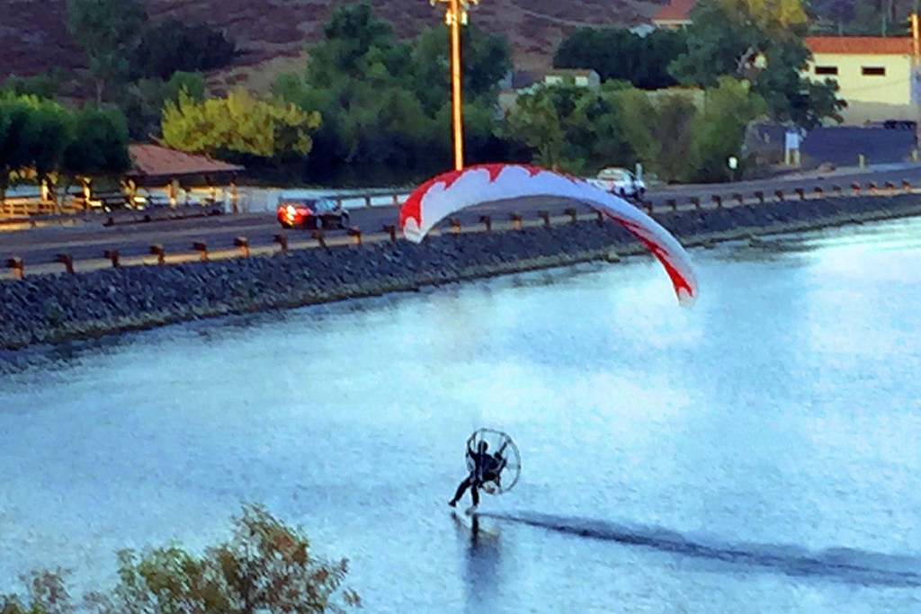 A motor-powered hang glider (also known as paramotor) was seen flying across the lake several times last month. It was flown by Paolo Frezza, seen in this photo by Dave Guthery near the North Causeway.