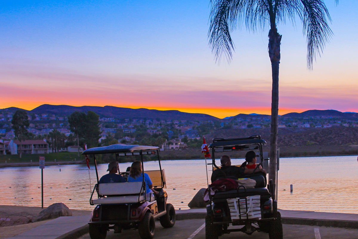 Residents in golf carts take a few moments to enjoy the sunset from Sunset Beach. Photo by Donna Ritchie.