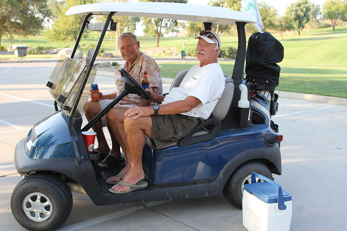 Hugh Wagoner and Bill Iverson take a break to have a cold drink and watch the sunset from the Golf Course parking lot. Hugh has lived in Canyon Lake for 30 years, Bill for 17. Photo by Donna Ritchie.