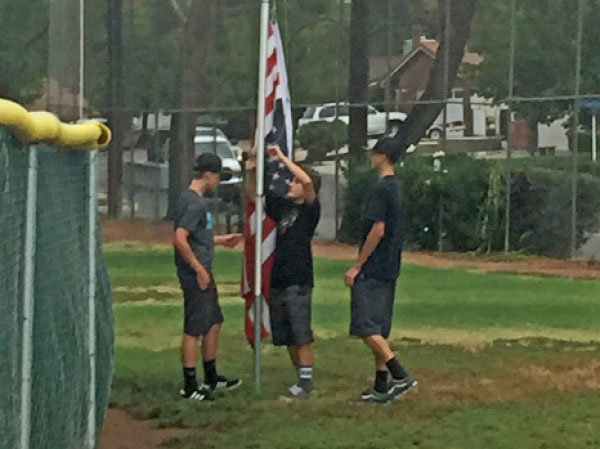 Conner Felt and Ethan Clark watch as Justin Gerlek loosens the U.S. flag trom the pole at Gault Field. The three friends had noticed the flag hanging upside down and almost dragging on the ground after the September 9 storm.