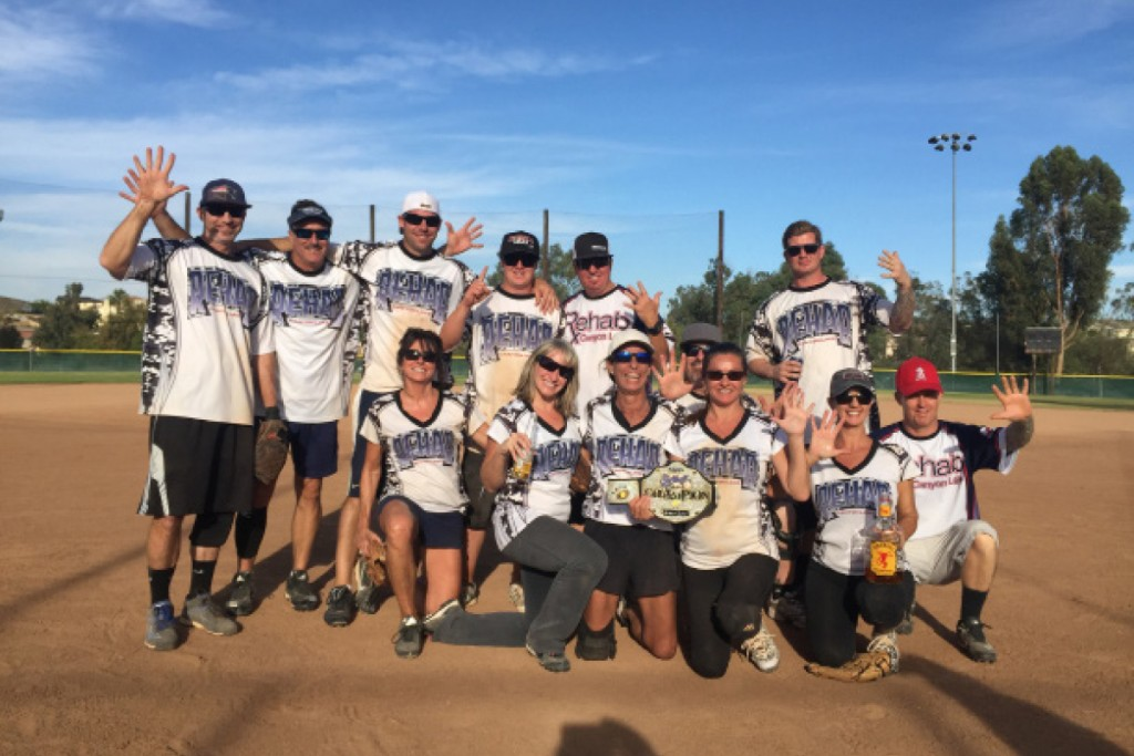 """The Canyon Lake co-ed softball team """"Rehab"""" won the winter championship for the second season in a row. Player Gina Pinto says that's never been done before. Team """"Rehab"""" has won the coveted belt five times since joining the club 10 years ago. """"It was a tough couple of games, but we pulled it off,"""" says Gina. Pictured in back row from left are Matt Nee, Rob Ehlers, Josh DeGonia, Broc Pinto-Dudley, Brandon Dudley, Mike Cuicchi and James Tiffie. In front row from left are Joanne Pinto, Deanna Felt, Nancy Pinto, Gina Pinto, Mona Cuicchi, and Josh Tomlin."""